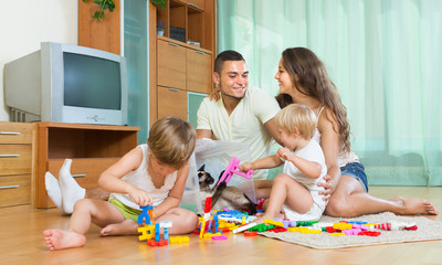Family of four at home with toys