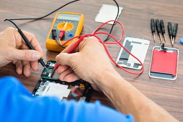 Technician Repairing Cellphone With Multimeter
