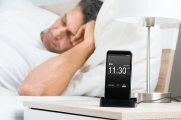 Mature Man On Bed With Alarm On Cellphone Screen