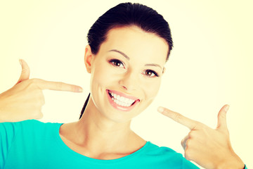 Beautiful woman pointing on her white teeth.