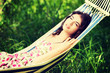 Young woman in dress relaxing in a hammock.