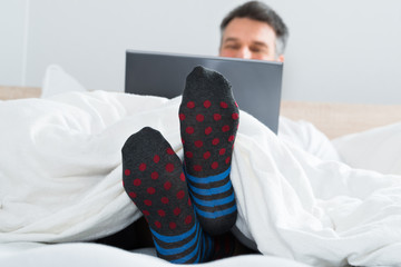 Man With Socks In His Leg Using A Laptop