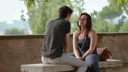 a boy and a girl on a bench on the first date - love