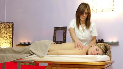 masseuse performs  a relaxing massage to a client - spa