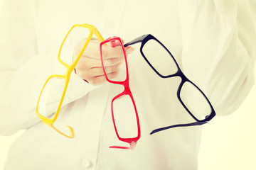 Woman holding three different pair of eyeglasses