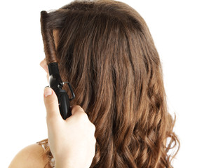 Stylist using curling iron for hair curls, close-up, isolated