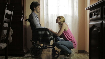 wife holding hands and caresses her depressed husband disabled