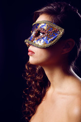 Beautiful girl with masquerade mask on dark background