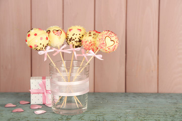 Tasty cake pops and gift on wooden background