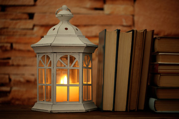 Books and decorative lantern on table and brick wall background