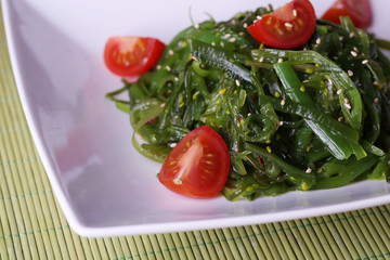 Seaweed salad with slices of cherry tomato