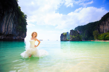 blonde bride stand in seawater
