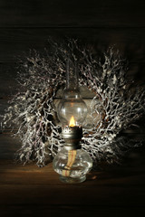 Kerosene lamp with wreath on rustic wooden planks background
