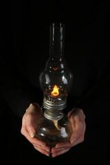 Kerosene lamp in female hands on dark background