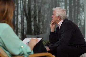 Sad man talking with psychologist