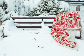 Warm plaid on bench in park in winter time