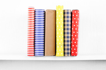 Colorful covered books on bookshelf and white wall background