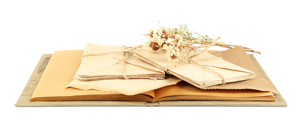 Old letters with dry flowers and book isolated on white