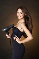 Beautiful young woman with long hair holding hair dryer