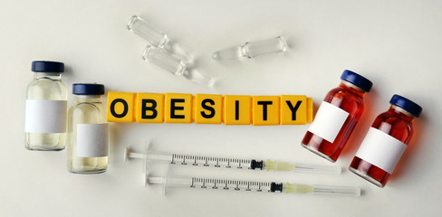 Obesity word and medical equipment on light background