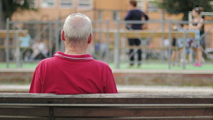 Lonely and sad old men on a bench, backfacing