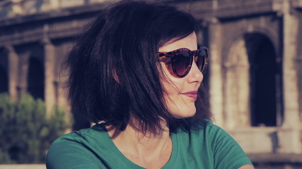 beautiful tourist (woman) with sunglasses  smiling at the camera near Colosseum