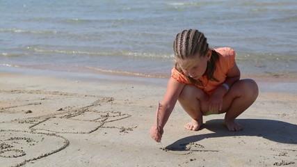 little girl playing on beach near sea