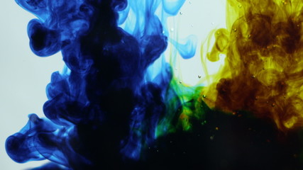 Abstract dynamic yellow and blue ink creating green