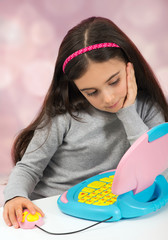 Little girl playing on a toy laptop computer