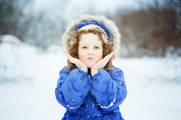 Happy little girl sends a kiss, playing in the snow park.