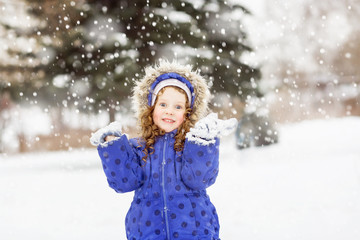 Surprised funny girl raised her hands in the air, catching snowf