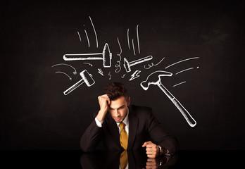 Depressed businessman sitting under hammer marks