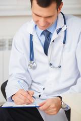 Portrait of confident doctor writing a prescription.