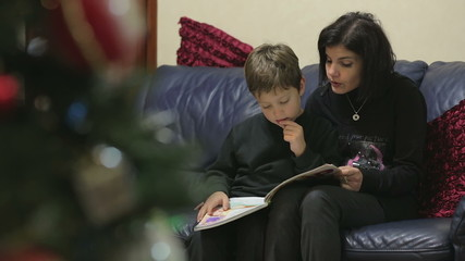 Mom and little son reading the stories about the legend of the Christmas