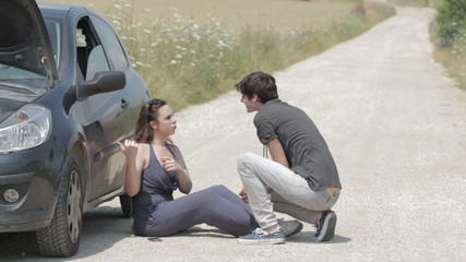 man helps a woman with her broken down car