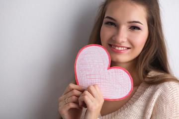 Portrait of beautiful happy woman holding a symbol heart.