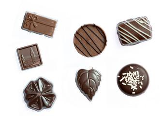Différents bonbons en chocolat sur fond blanc