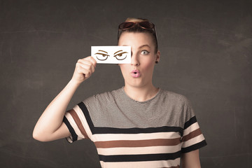 Young person holding paper with angry eye drawing
