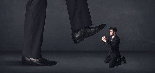 Giant person stepping on a little businessman concept