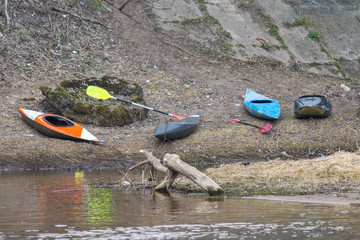 Kayaks are on the banks of the river