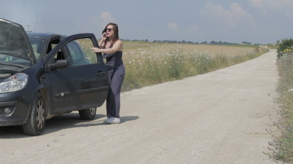 woman with the broken down car on a country road ,call a auto mechanic