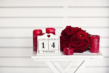 red roses lay on the table near calendar  with the date of Febru