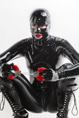 sitting woman wearing latex clothes with handcuffs
