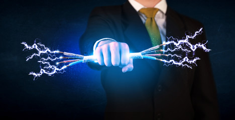 Business person holding electrical powered wires