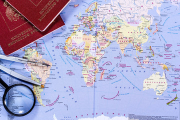 open world map with magnifying glass, compasses and passport