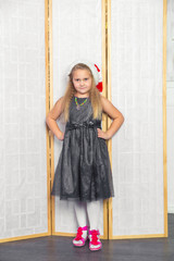 Little girl with white hair in a gray dress red shoes posing sta