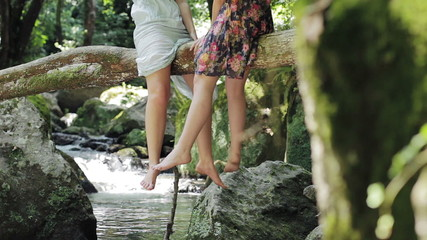 live in harmony with the nature - legs dangling from a tree near a stream