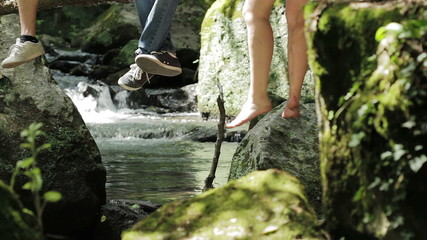 live in contact with the nature - legs dangling from a tree near a stream