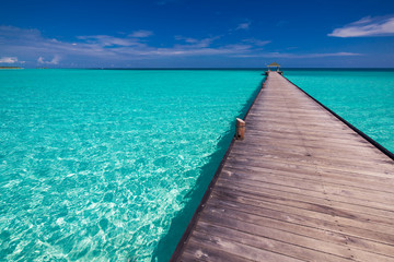 Long jetty over lagoon in Maldives with amazing clean water