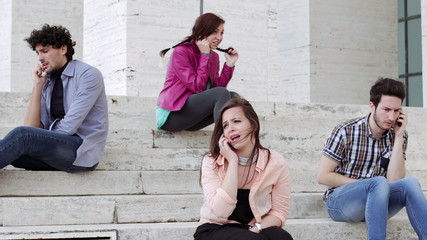 Four young people are on the phone sitting on a staircase - technology